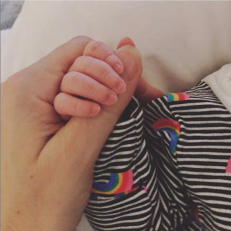 Holding the hand of her son Max earlier this month.